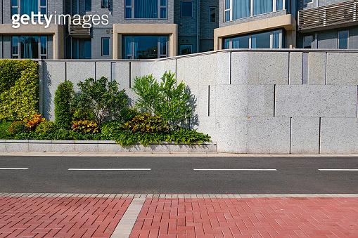 White empty brick cracked wall background on sidewalk of city