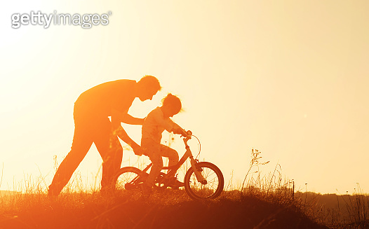 Silhouette of father teaching his daughter to ride a bike at sunset