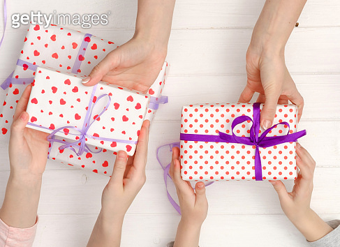 Top view of female hands holding gifts for different occasions