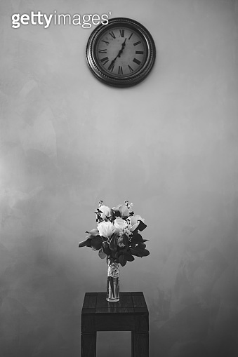 bridal bouquet of white tulips, delphinium, salal, limonium and lace ribbons in glass vase on the wooden stool under wall clock