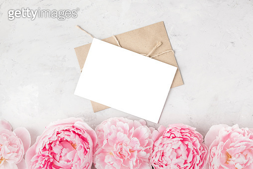 Blank greeting card and envelope with pink peony flowers on concrete background. Wedding invitation. Flat lay. Mock up