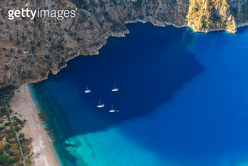 The Butterfly Valley (kelebekler vadisi) with sandy beach and yachts in the city of Oludeniz or Fethiye, Turkey