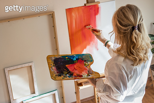 Woman painting on canvas in workshop