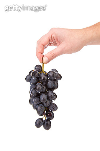 Black grapes in hand.