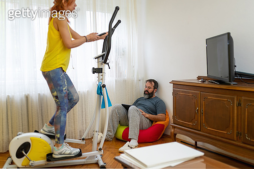 Woman exercising on elliptical trainer while her partner is using digital tablet in the living room