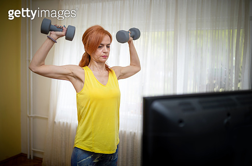 Woman lifting dumbbells in the living room and watching TV