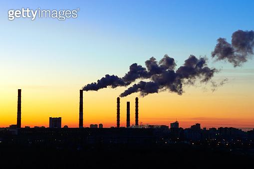 pipes smoke factories at sunset