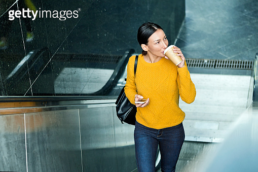Woman drinking coffee cup and moving up on escalator