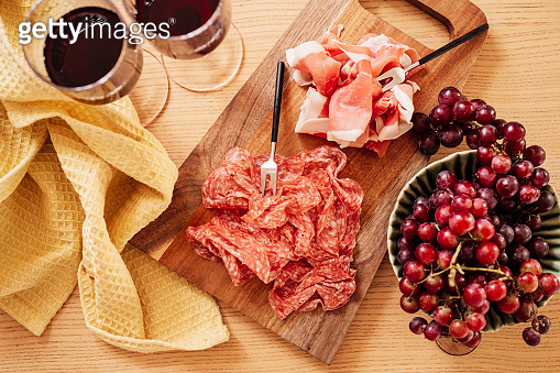 Red wine and cold cuts meat indoors on table