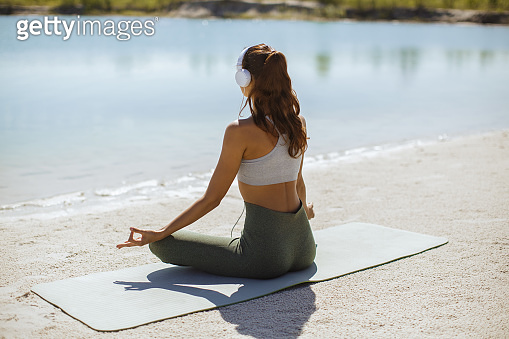 Woman Meditating in Yoga pose on the Beach