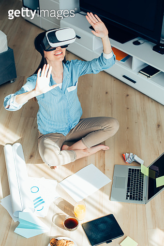 Excited lady putting hands up while exploring virtual reality