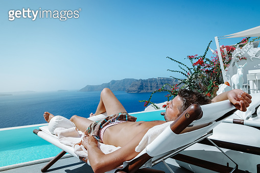 Santorini Greece Oia, young men in swim short relaxing in the pool looking out over the caldera of Santorini Island greece, infinity pool Greece