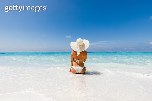 Rear view of carefree woman relaxing in water on the beach.