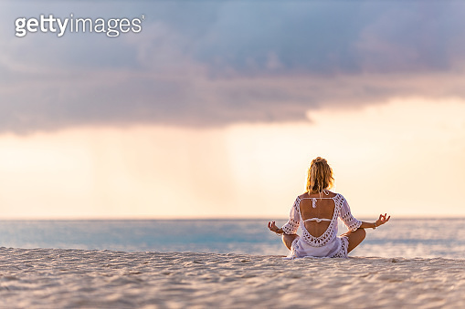 Back view of relaxed woman meditating on the beach.