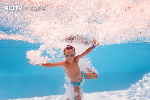 Cute boy splash in a pool after jump, make bubbles