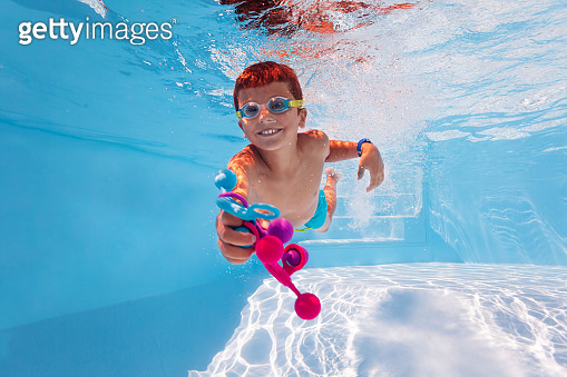Child dive in a pool collecting toys wear googles