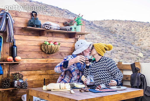 Two senior hikers with hats while kissing each other.  A 70-year-old couple take a break with food and drinks after a hike in the mountains
