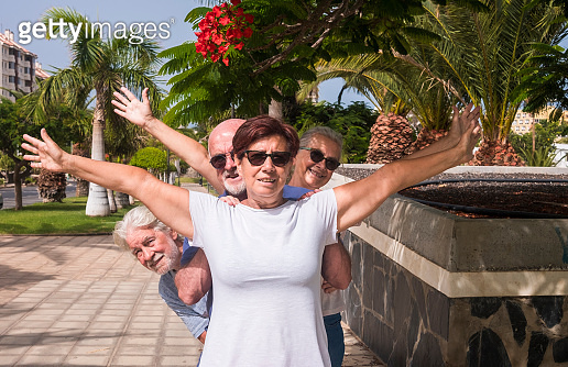 Cheerful group of senior friends enjoying vacation - four retired people in public park with palms trees and blossom plants - active retirement concept