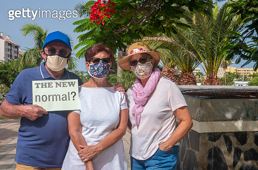 Three senior people standing in public park wearing face mask due to coronavirus, holding the message new normal life - blue sky and blossom plants in background