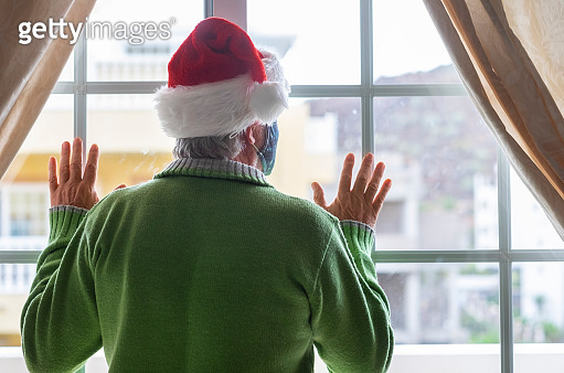 Rear view of a senior man with a Santa hat, green sweater and face mask staying at home behind the window looking out. Concept of loneliness for lockdown due to the covid-19 coronavirus