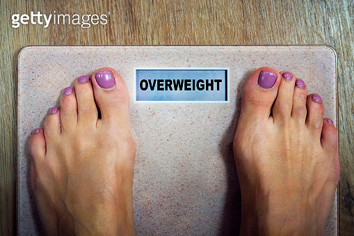 Top-down view to female bare feet standing on scale with written word overweight on display. Concept fitness and loosing weight. Woman needs to become slimmer. Scale showing dieting and shaping time