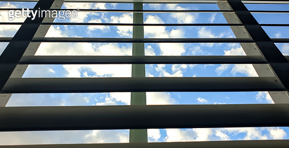 blue sky with cloud patterns through the window blinds