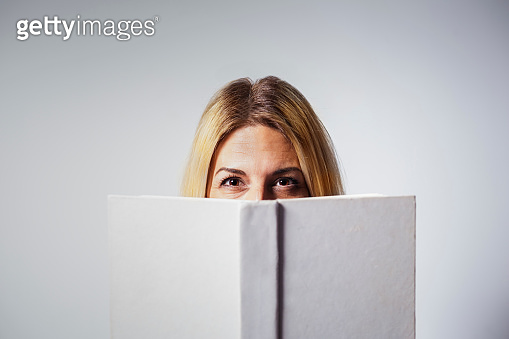 Blonde woman holding a white hardcover book