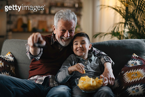 Grandfather and grandson watching television
