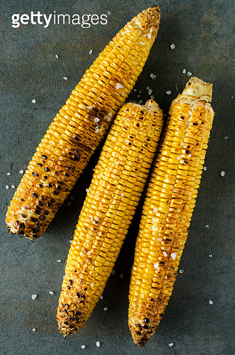 Vertical image.Top view of roasted corn with salt on the drk grey surface.Tasty snack
