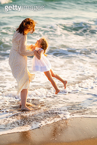 mom and kid walking on sea beach with big waves in windy weather. happy family