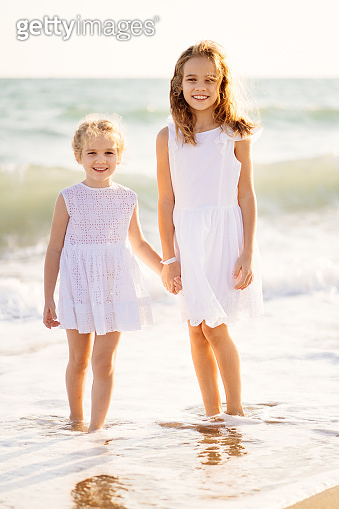 kids, girls walking on beach with big waves in windy weather. vacation to sea.