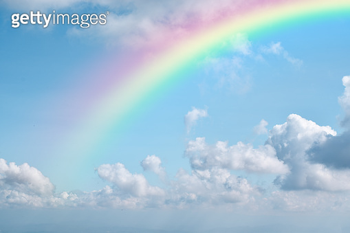 Rainbow on blue sky with white cloud background.