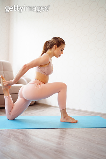girl with a beautiful athletic body makes lunges, does yoga exercises at home.