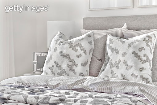 Modern bed with pillows and wool blankets near lamps