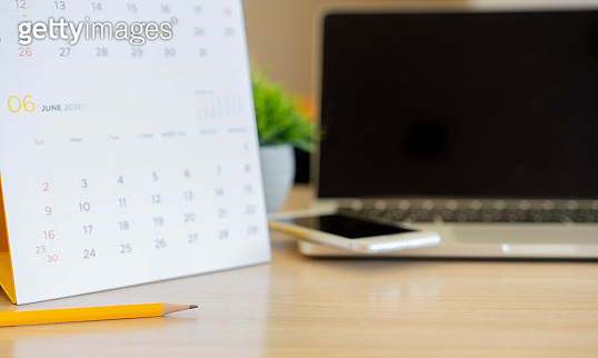close up yellow pencil on desk with laptop, smartphone and calendar at home office for work from home and business appointment concept