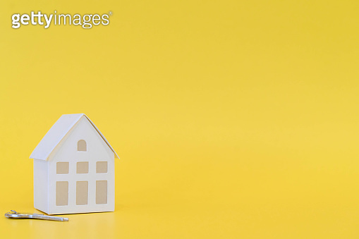 close up home model with key on yellow color background with space for money management ,home loan refinance and personal financial concept