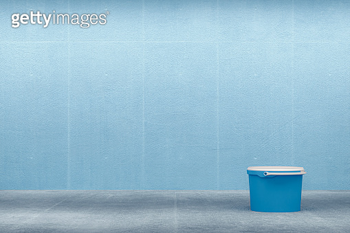 Blue painted concrete wall with paint can
