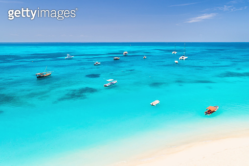 Aerial view of the fishing boats on tropical sea coast with white sandy beach at sunset. Summer travel and holidays in Zanzibar, Africa. Landscape with boat, yacht, clear water, blue sky. Top view