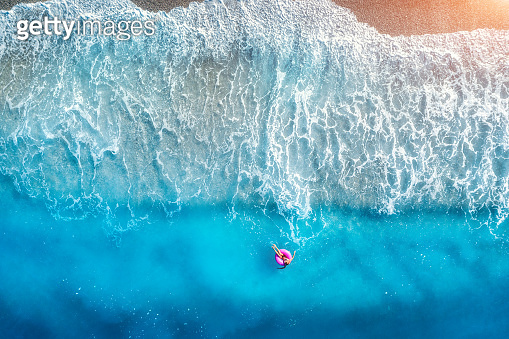 Aerial view of a young woman swimming with the donut swim ring in transparent blue sea with waves at sunset in summer. Tropical landscape with girl, azure water, sandy beach. View from above. Travel