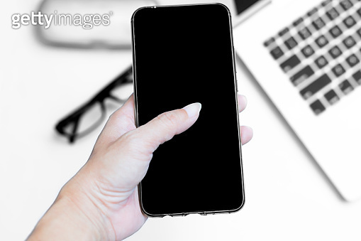 Hand holding blank screen smart phone on white background. Top view with copy space