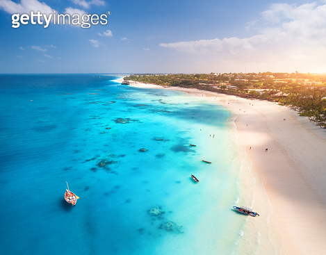 Aerial view of the fishing boats on tropical sea coast with white sandy beach at sunset. Summer travel in Zanzibar, Africa. Landscape with boat, yacht, clear blue water, green palm trees. Top view