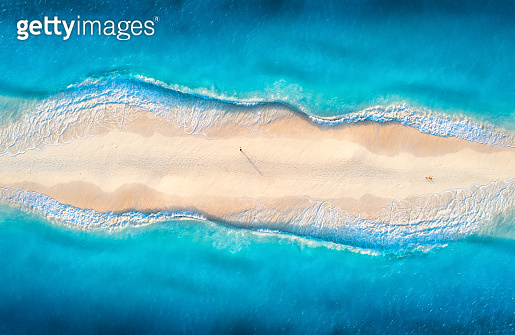 Aerial view of transparent blue sea with waves on the both sides and people on sandy beach at sunset. Summer travel in Zanzibar, Africa. Tropical landscape with lagoon, white sand and ocean. Top view