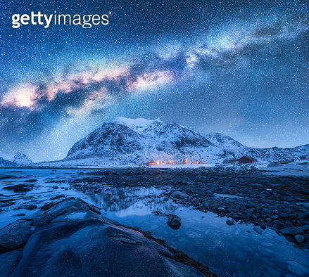 Milky Way over snow covered mountains and rocky beach in winter at night. Lofoten Islands, Norway. Cosmic landscape with starry sky, water, stones, snowy rocks, bright milky way and city lights. Space