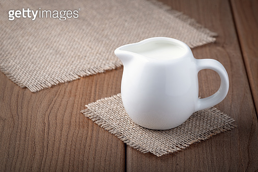 White jug with milk on a wooden rustic background.