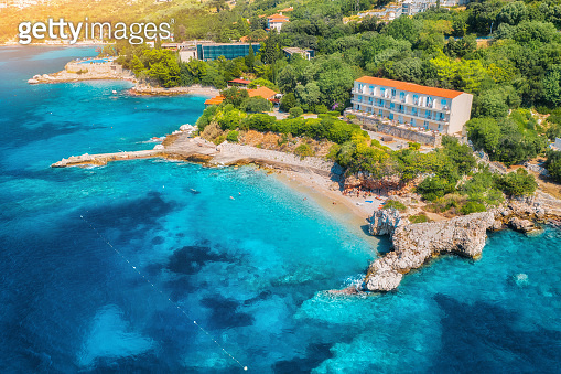 Aerial view with beautiful sea coast, sandy beach, clear blue water, hotels and green trees at sunset. Summer tropical landscape. Top view of blue sea, buildings, rocks and forest. Luxury resort