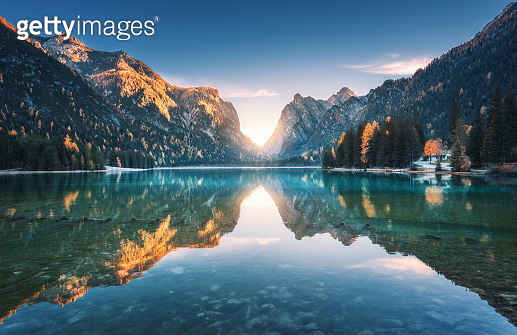 Mountain lake at sunset in autumn. Landscape with lake, blue sky with gold sunlight, reflection in water, trees with colorful leaves, high rocks in fall. Travel in Dolomites, Italy. Nature