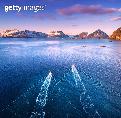 Aerial view of two fishing boats, rocks in the blue sea, snowy mountains and colorful sky with clouds at sunset in winter in Lofoten islands, Norway, Landscape with motorboats. Top view. Travel