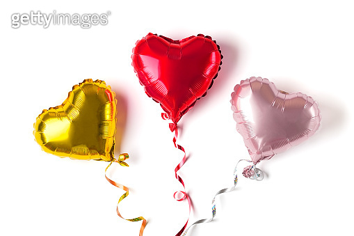 set of three inflatable heart in golden, red, matte pink color isolated on white background Flat lay Top view Holiday card Happy Valentine's day, Birthday party concept Love in the air