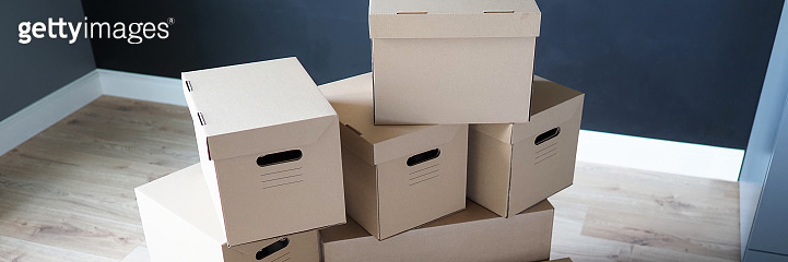 Pile of carton boxes standing in the middle of empty room in new house