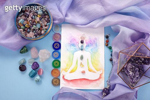 Natural crystals and pendulum on pastel silk background. Reiki background with card.